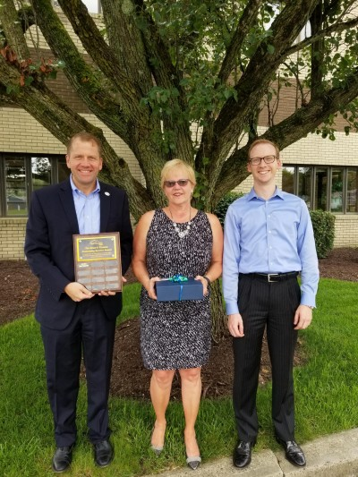 Donna Thomas-Hart is presented with a plaque and award as the first recipient of the Brian F. Thomas Community Service Award.  Presenting are David M. Thomas, President and CEO (left) and Chase Thomas, son of the late Brian F. Thomas, and Associate Accountant at Clear Mountain Bank.