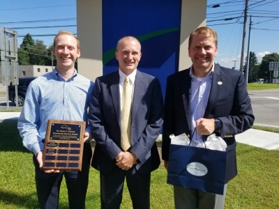Tim Calvert (center) is presented with a plaque and award as the 2019 recipient of the Brian F. Thomas Community Service Award. Presenting are Chase Thomas (left), son of the late Brian F. Thomas and controller at Clear Mountain Bank, and David M. Thomas, president and CEO of the bank.
